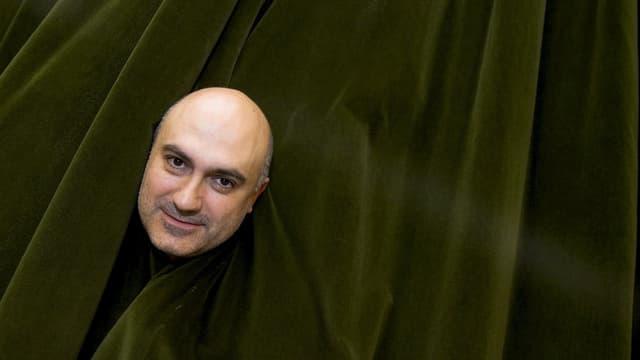 Regisseur Calixto Bieito blickt Betrachter durch Loch in Theatervorhang an.
