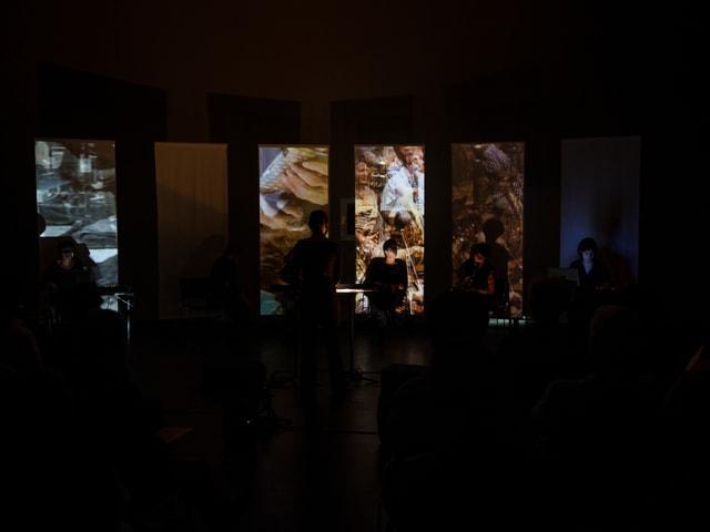 Ein dunkler Raum, der nur durch eine Videoinstallation beleuchtet wird.