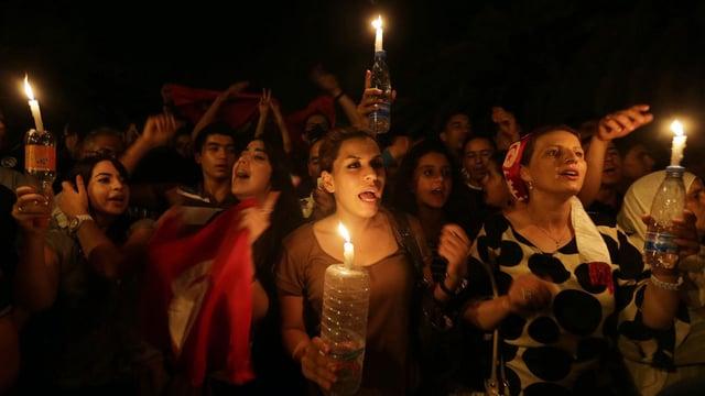 Demonstrierende Regierungsgegner in der Nacht mit Kerzen in der Hand.