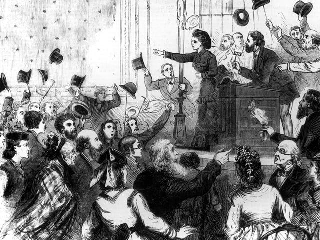 Zeichnung: Victoria Woodhall steht erhöht und mit ausgestrecktem Arm und blickt in eine Menge jubelnder Menschen, die teilweise ihre Hüte in dei Luft werfen.