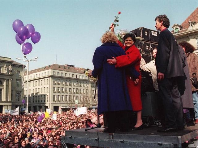 Dreifuss und Brunner stehen auf einem Podium vor der Menschenmenge auf dem Bundesplatz. Dreifuss hält eine rote Rose hoch.