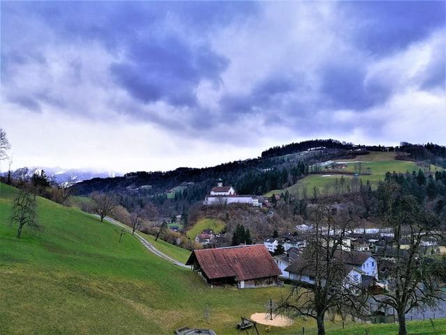 Hügelige Landschaft mit grünen Wiesen und ein paar Bäumen, im Tal Häuser und das Kloster.