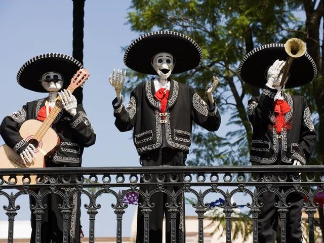 Drei Skelett-Figuren, die Musik spielen