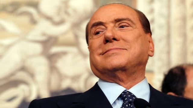 Berlusconi hebt den Kopf und schaut erleichtert auf die untere Seite.