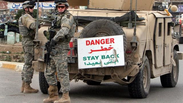 Soldaten vor einem Geländewagen.