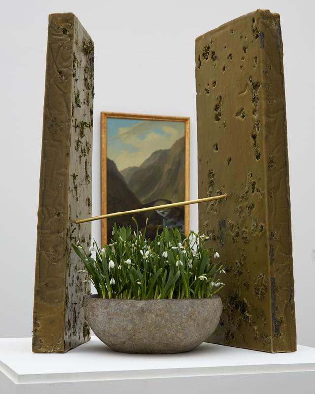 Frühlingsblumen in Schale zwischen zwei Wänden vor Tallandschaft