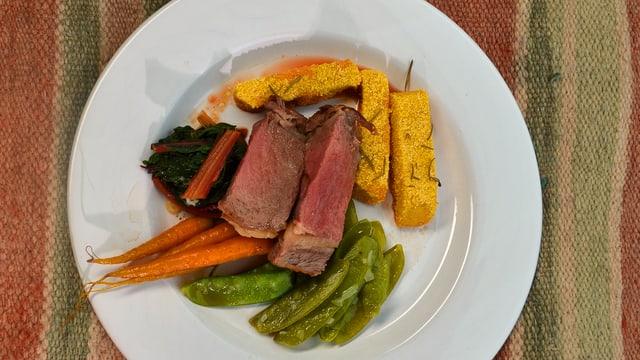 Hauptspeisenteller mit Fleisch und Gemüse.