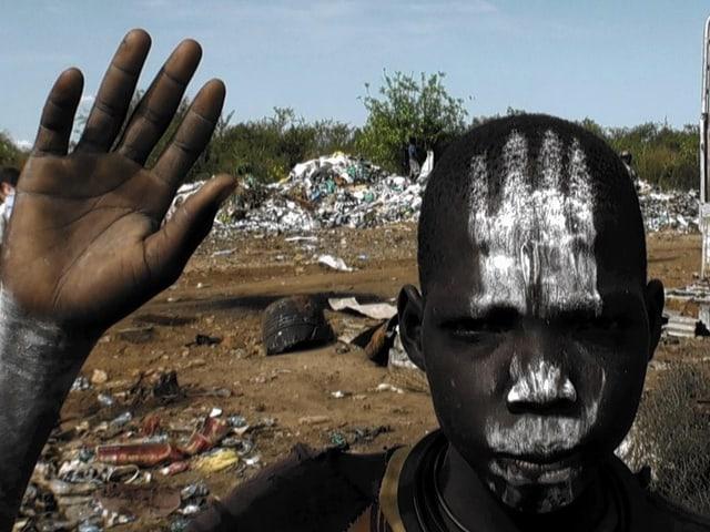 Ein sudanesischer Junge hebt seine Hand. Er blickt direkt in die Kamera und hat eine Gesichtsbemalung.