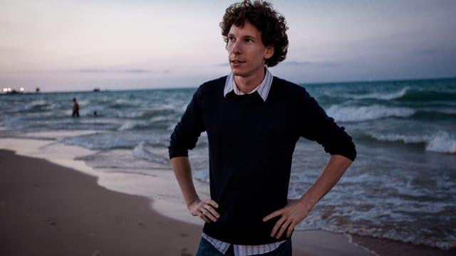Mann mit Locken am Strand, Abenddämmerung