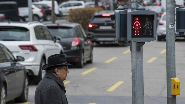 Ein Mann steht neben einer Autostrasse.