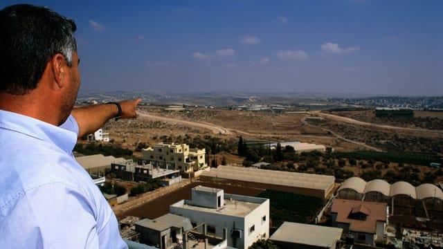 Ein Palästinenser zeigt auf einen Zaun im Westjordanland.