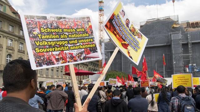 Rückenansicht von demonstrierenden Tamilen in Bern mit Protestschildern.