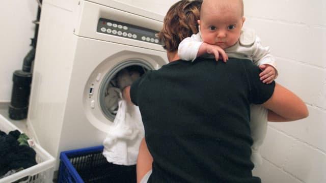 Frau mit Baby leert eine Waschmaschine.
