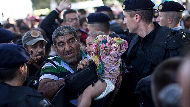 Polizia corata fraina ils migrants al cunfin.