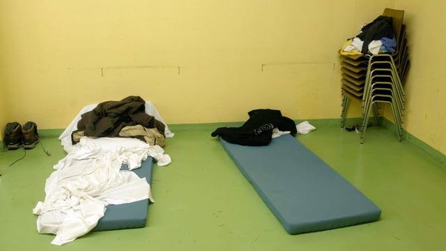 Zwei Matratzen liegen auf dem grünen Boden eines kargen Raums für Obdachlose als Notunterkunft bereit.