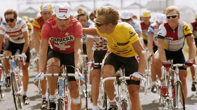 Eine Gruppe von Rennfahrerfahrern unterwegs auf der letzten Etappe, Zimmermann trägt ein rotes Trikot mit dem Schweizer Kreuz darauf, und einem weissen Käppi. Der Amerikaner trägt das gelbe Trikot und hat eine Sonnenbrille auf.