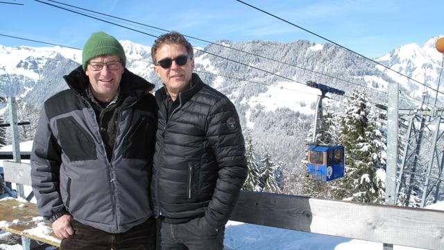 zwei Männer vor Seilbahn und Bergpanorama