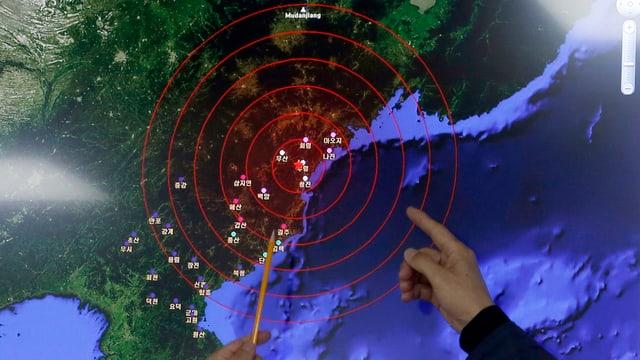 Zwei Hände zeigen auf eine Karte der Korea-Halbinsel.