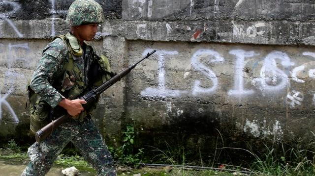Soldat geht an einem Schriftzug «ISIS» vorbei.