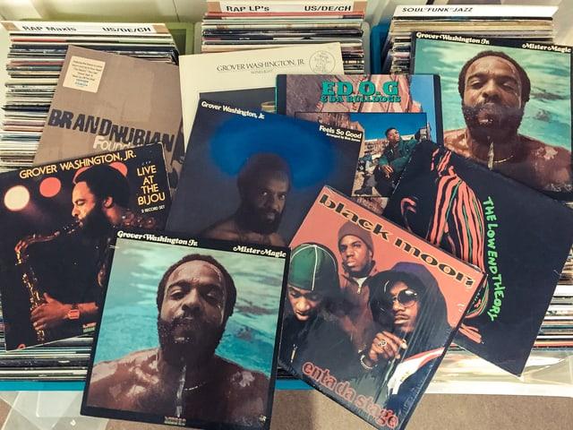 Einige Schallplatten liegen kreuz und quer auf Plattenkisten.