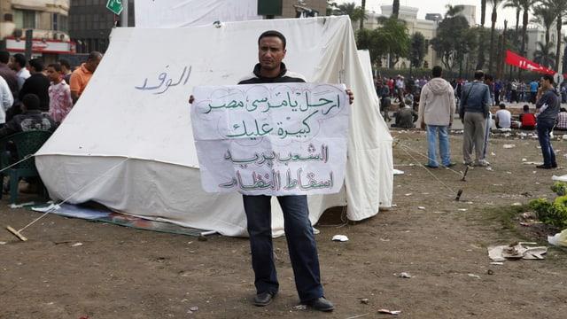 Ein Mann hält ein Plakat mit arabischer Schrift.