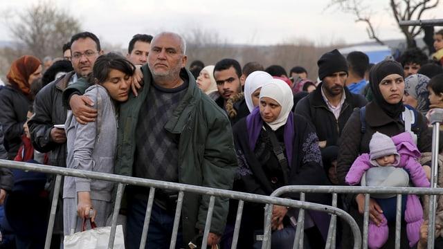 Flüchtlinge hinter einer Absperrung
