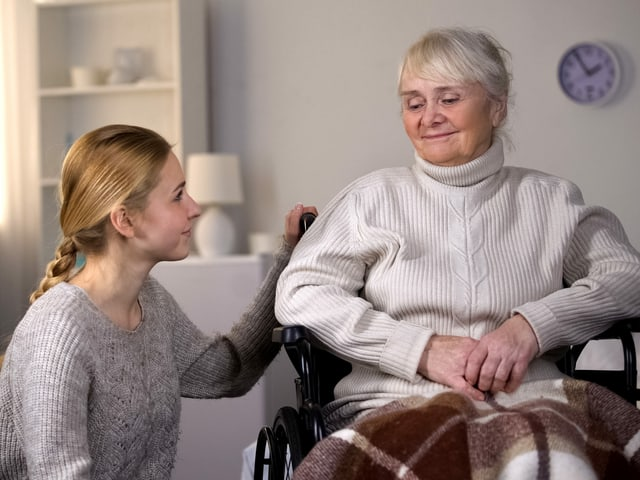 Junge Frau beugt sich fürsorglich zu Seniorin im Rollstuhl hin.