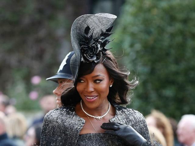Naomi Campbell mit üppigem schwarzem Hut.