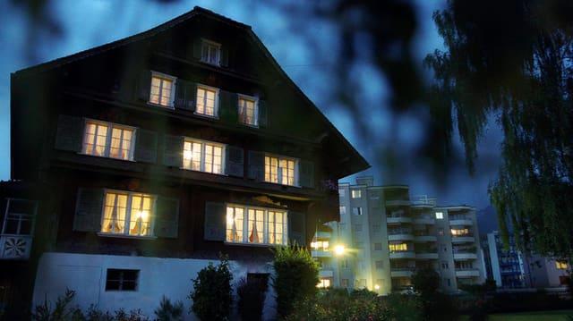 Altes Holzhaus mit hell beleuchteten Fenstern vor dunklem Nachthimmel.