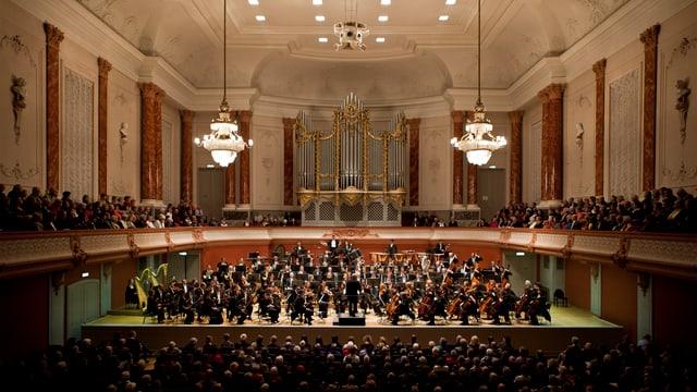 Auf der Bühne das Orchester, davor und seitlich auf dem Balkon das Publikum. Von der Decke hängen zwei Kronleuchter in den Saal hinein, im Hintergrund eine grosse Orgel.