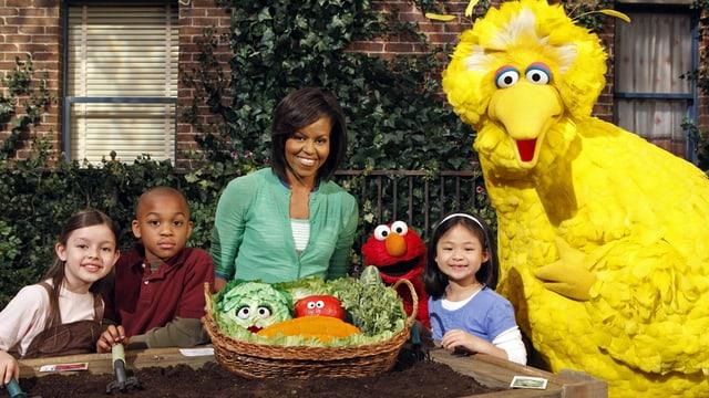 Michelle Obama in der Sesamstrasse, vor ihr un den Kindern ein Korb voller Gemüse.