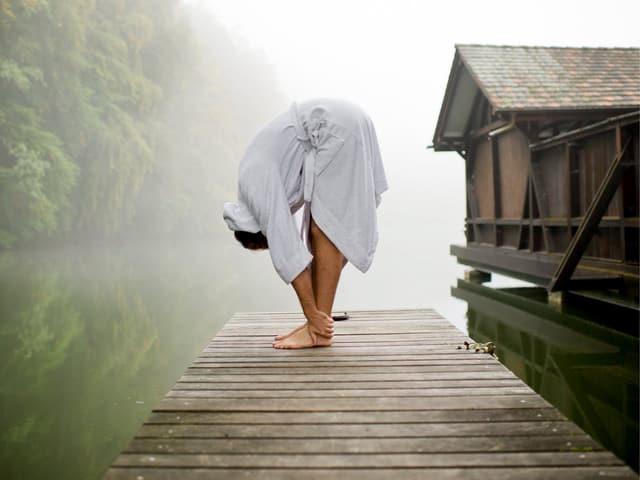 Mann macht Yoga auf einem Steeg am See.