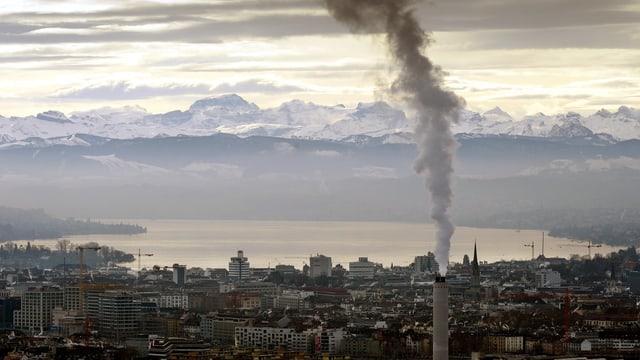 Blick auf Zürich, im Hintergrund Schneeberge, im Vordergrund ein dampfender Schlot.