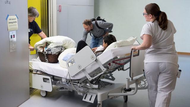 Pflegepersonal schiebt Bett mit Patientin in Lift.