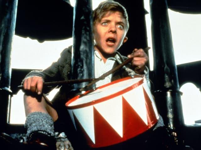 Ein junge trommel auf einer rot-weissen Trommel.