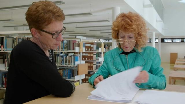Zwei Frauen stehen in einer Bibliothek an einem Tisch und schauen in ein Dokument.
