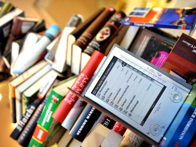 E-Book und ein Stapel analoge Bücher.