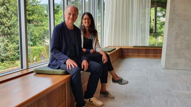 Mann und Frau sitzen auf Fensterbank