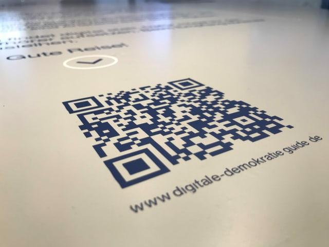 L'entrada en l'exposiziun e in QR Code. Il telefonin fa part da l'exposiziun.