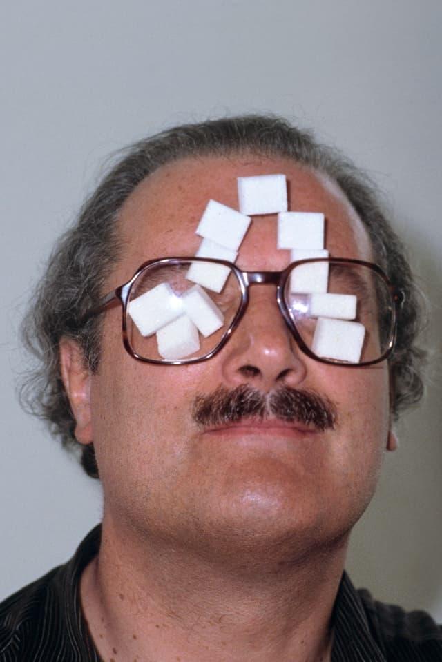 Der Schweizer Künstler André Thomkins steckt sich in einer Pause während des Aufbaus seiner Ausstellung, Zuckerstücke hinter die Brillengläser. Städtische Galerie zum Strauhof, Zürich, 9. Juni 1982.