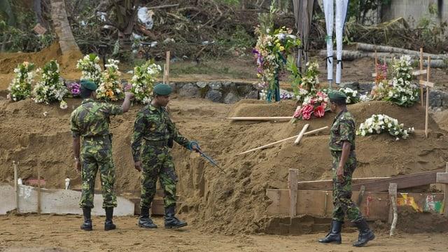 Vor einem geplanten Massenbegräbnis in Negombo suchen Soldaten die Gegend nach Sprengstoff ab.