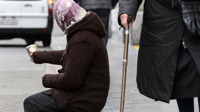 Frau sitzt auf der Strasse und und bettelt mit einem Pappbecher.