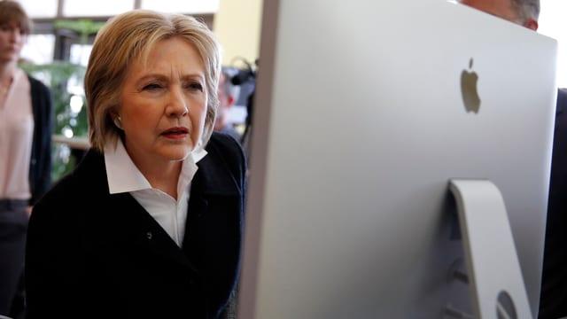 Clinton mit gerunzelten Augenbrauen und leicht vorgebeugt an einem grossen Bildschirm sitzend.