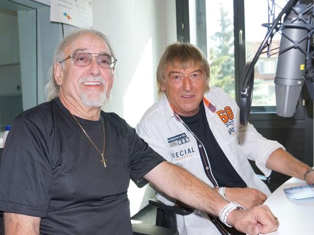 Zwei Männer sitzen im Sendestudio hinter Mikrofon.