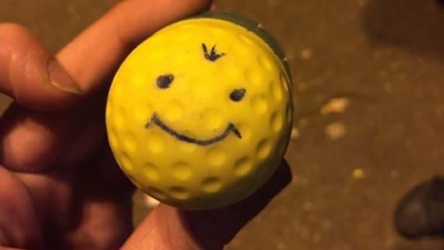 Gelbes rundes Gummigeschoss mit aufgezeichnetem lächelndem Gesicht