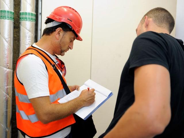 Zwei Männer stehen zusammen, ein Gewerkschaftssekretär und ein Arbeiter, und schauen zusammen auf ein Formular.