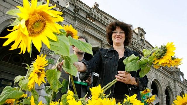 Eine Frau steht hinter vielen Sonnenblumen.