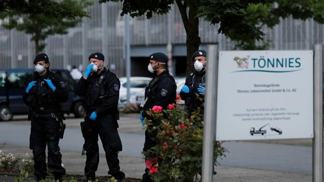 Polizisten mit Gesichtsmaske vor dem Tönnies-Betriebsgebäude.