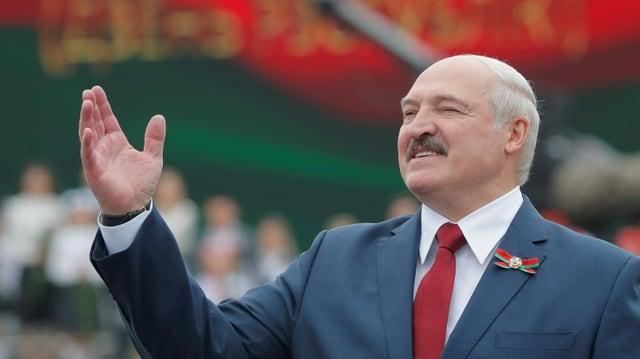 Lukaschenko mit erhobener Hand.