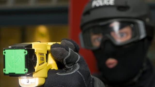 Polizist zielt mit Taser.